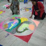 Two woman making a rangoli