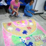 two girls making a rangoli