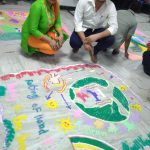 A man and a woman making a rangoli